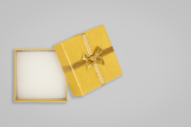 Top view of opened yellow gift box on glay background