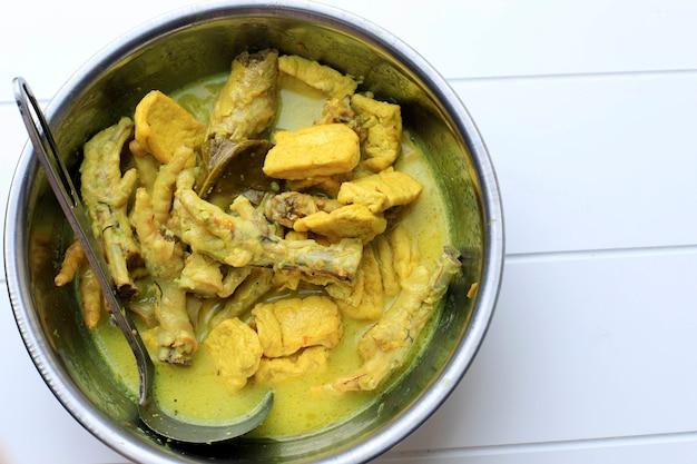 Вид сверху опор чекер аям кампунг с тофу в миске. опор - это желтый карри, обычно из мелаю, индонезия или малайзии. копировать пространство для текста