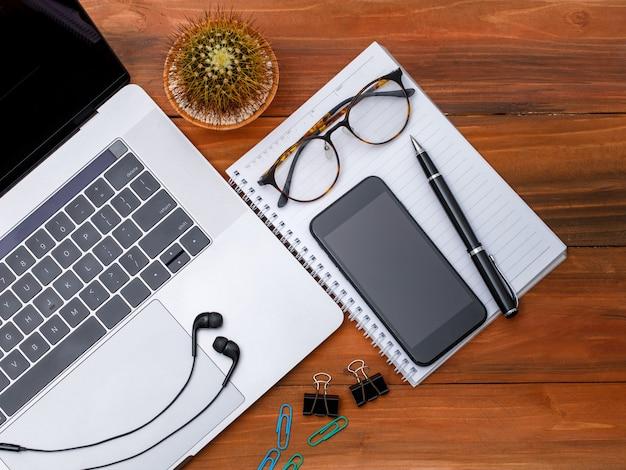 コピースペースと木の背景に空白の画面のスマートフォンとラップトップノートブックコンピューターの上面図またはトップダウンショット。ビジネスアイデアと創造的な作業コンセプト。