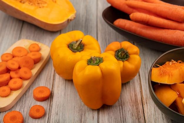 Vista dall'alto di peperoni arancioni con fette di zucca su una ciotola con carote tritate su una tavola da cucina in legno su una parete di legno grigia