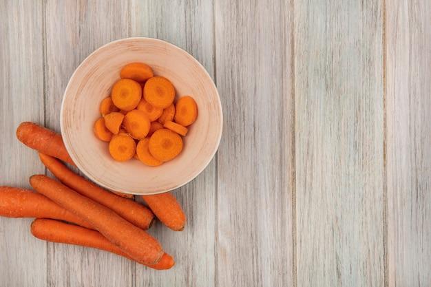 Vista dall'alto di carote tritate arancioni su una ciotola con carote isolate su una superficie di legno grigia con spazio di copia