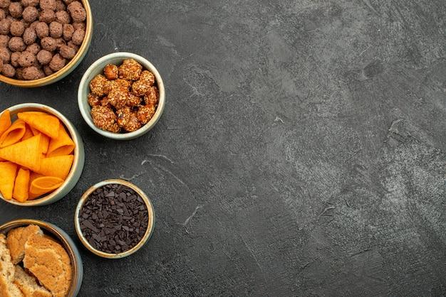 회색 표면 식사 스낵 조식 너트에 달콤한 견과류와 초콜릿 플레이크가 있는 상위 뷰 오렌지 cips