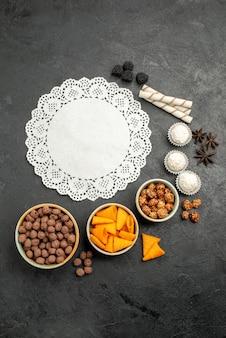 灰色の机の上の甘いナッツとフレークとオレンジ色のcipsスナック食事朝食ナッツの上面図
