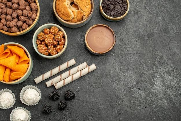 Cips arancioni vista dall'alto con noci dolci e scaglie di cioccolato su dado per la colazione con snack da pavimento grigio scuro