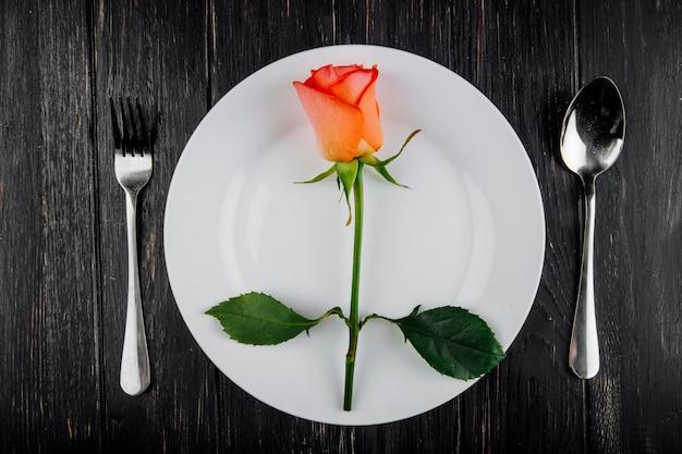 La vista superiore di colore arancio è aumentato con il cucchiaio e la forchetta su un piatto bianco su fondo di legno scuro