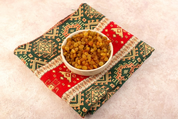 A top view orange dried raisins inside round plate on colorful designed carpet on pink