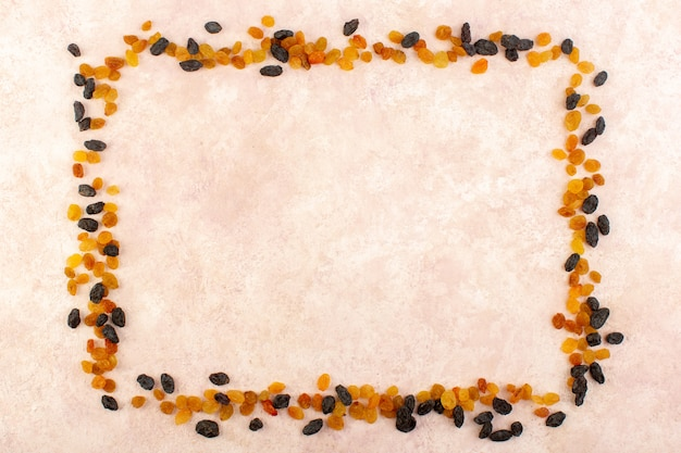A top view orange dried raisins with black dried fruits shaping square on pink