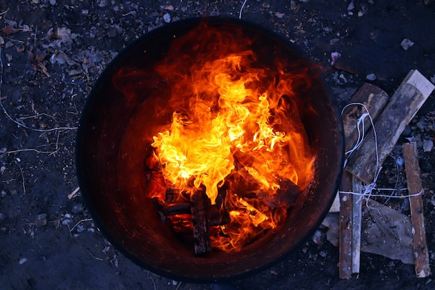 Top view of an orange flame in an old iron barrel