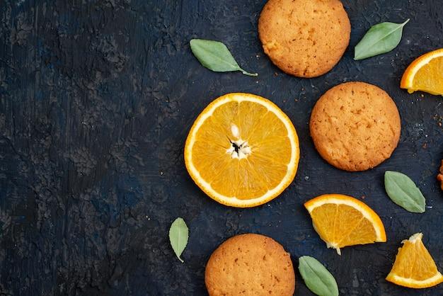 Una vista dall'alto biscotti aromatizzati all'arancia con fette d'arancia fresche sullo sfondo scuro dello zucchero del biscotto del biscotto
