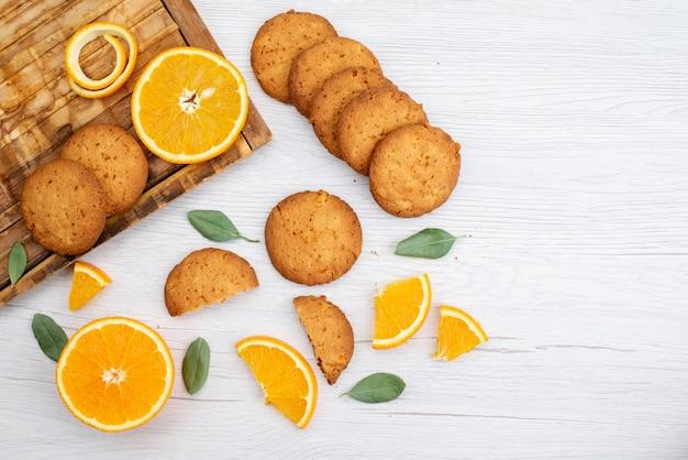 Una vista dall'alto di biscotti aromatizzati all'arancia con fette d'arancia fresche sul biscotto di frutta leggera scrivania