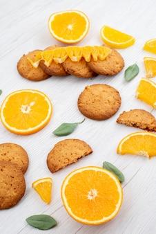 Una vista dall'alto biscotti aromatizzati all'arancia con fette d'arancia fresche sul biscotto di frutta leggero scrivania