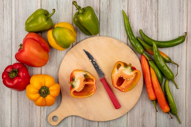 Top view of orange half bell peppers on a wooden kitchen board with knife with colorful peppers isolated on a grey wooden background
