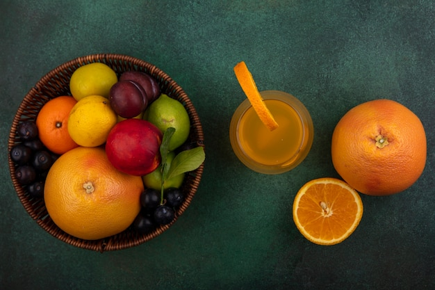 Top view orange juice in a glass with grapefruit  lime  lemon  peach  cherry plum  orange and plum in a basket on a green background
