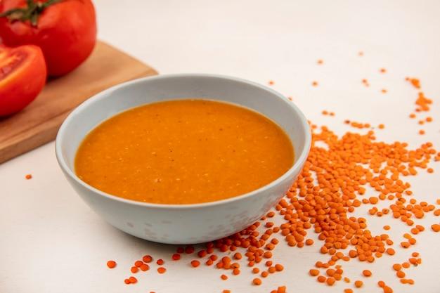 Vista dall'alto di zuppa di lenticchie arancione su una ciotola con i pomodori su una tavola da cucina in legno con lenticchie fresche isolato su una superficie bianca