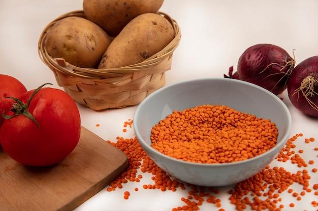 Vista dall'alto di lenticchie arancioni su una ciotola con patate su un secchio con pomodori su una tavola da cucina in legno con cipolle rosse isolato su un muro bianco