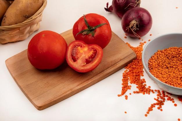 Vista dall'alto di lenticchie arancioni su una ciotola con pomodori su una tavola di cucina in legno con cipolle rosse isolate su un muro bianco