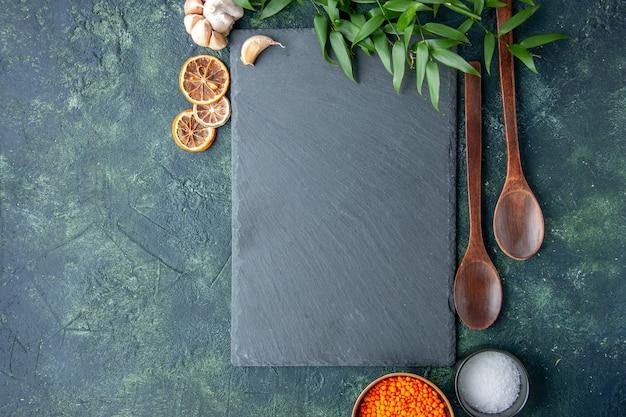 Vista dall'alto lenticchie arancioni con aglio e sale su sfondo blu scuro foto cibo piccante peperoncino colore zuppa di semi taglienti