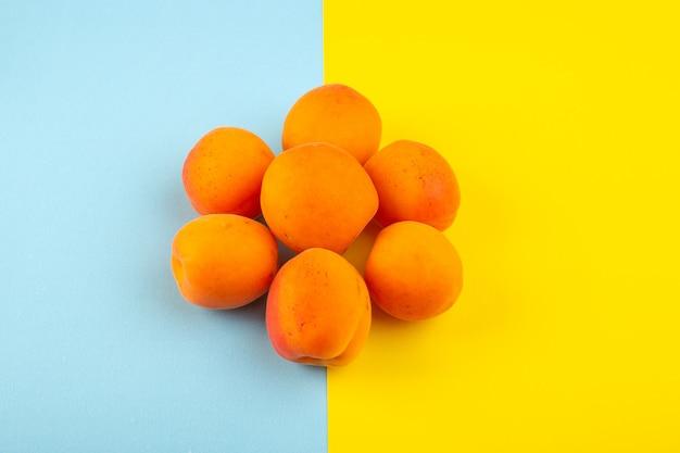 Una vista dall'alto le pesche arancioni aspre gustosi feti freschi allineati sullo sfondo blu-giallo ghiaccio frutta esotica estate succo
