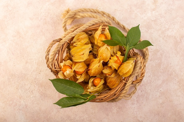 A top view orange peeled physalises inside basket