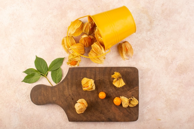 A top view orange peeled physalises inside bucket