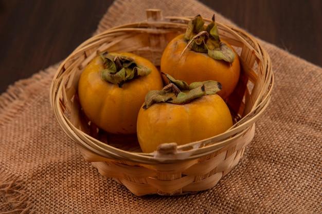 Vista dall'alto di frutti di cachi arancione su un secchio su un panno di sacco su un tavolo di legno