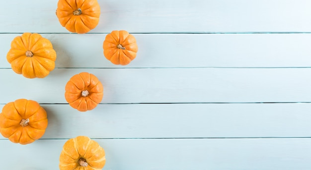 Top view of orange pumpkin on pastel wooden background with copy space for text. halloween, autumn decoration concept.