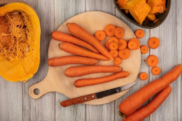 Vista dall'alto di carote di ortaggi a radice arancione su una tavola da cucina in legno con carote tritate con coltello con mezza zucca su una superficie di legno grigia