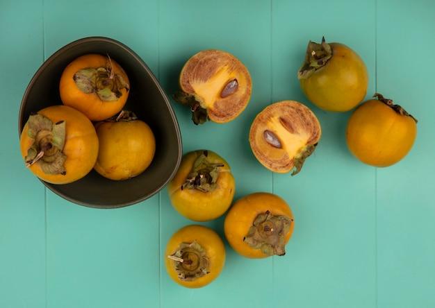 Vista dall'alto dei frutti di cachi tondeggiante arancione su una ciotola con frutti di cachi isolati su un tavolo di legno blu