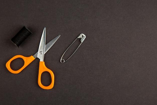 Вид сверху оранжевые ножницы на темном фоне