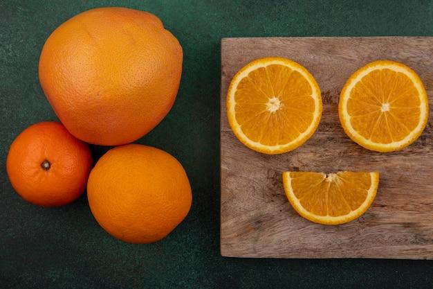 Vista dall'alto fette d'arancia sul tagliere con pompelmo su sfondo verde