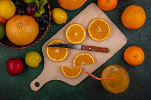 緑の背景の上のバスケットにナイフグレープフルーツライムレモンプラムと桃とまな板の上のオレンジスライスの上面図