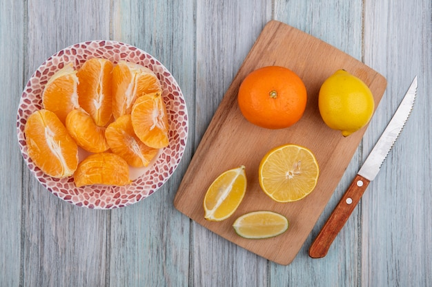Top view orange slices on plate with lemon wedges on cutting board with knife on gray background