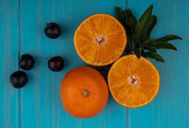Vista dall'alto fette d'arancia con prugna ciliegia su uno sfondo turchese