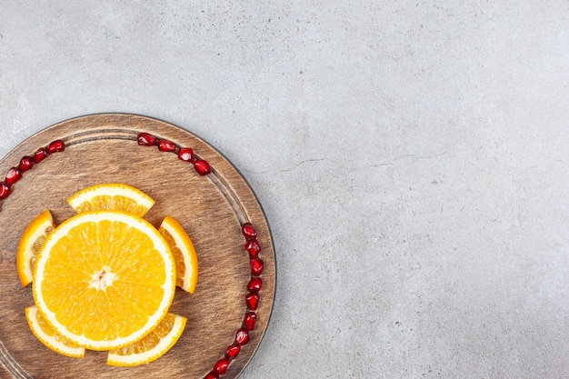 Top view of orange slices with pomegranate seeds on wooden board over grey surface.