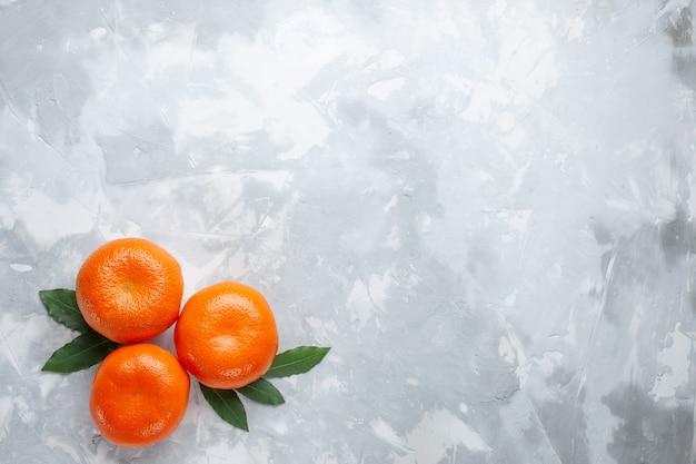 Vista dall'alto mandarini arancioni interi agrumi sulla scrivania bianca agrumi succo di frutta esotica