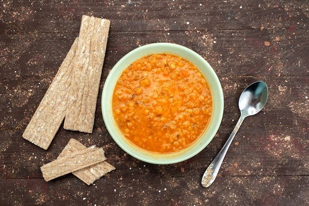 Вид сверху апельсин вкусный суп с крекерами и ложкой на коричневый, еда обед ужин суп