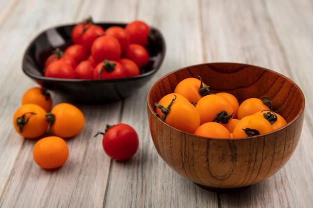 Vista dall'alto di pomodori arancioni su una ciotola di legno con pomodori rossi su una ciotola nera su una superficie di legno grigia