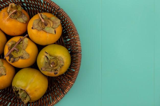 Vista dall'alto di frutti di cachi acerbi arancione su un secchio su un tavolo di legno blu con spazio di copia
