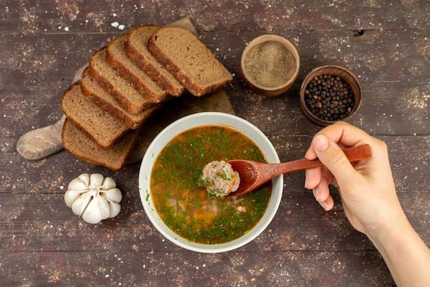 Вид сверху апельсиновый овощной суп с буханками хлеба и чесноком, съедаемым мужчиной на коричневом, еде