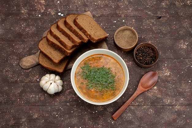 Top view orange vegetable soup with bread loafs and garlic on brown, food meal soup bread