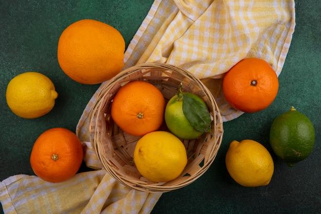 緑の背景に黄色の市松模様のタオルの上のバスケットにレモンとライムとオレンジ色の上面図