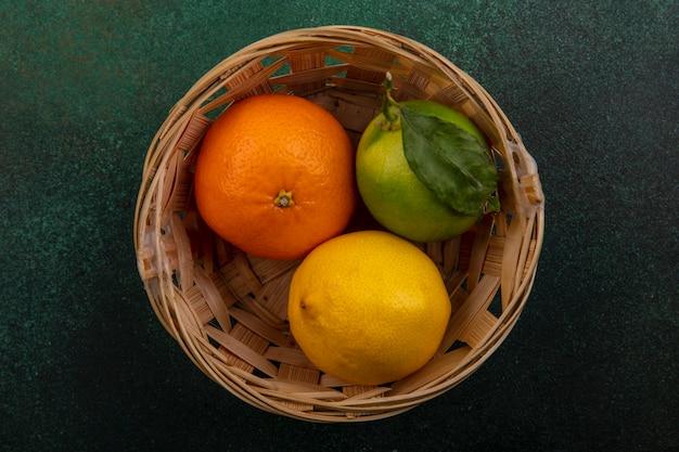 緑の背景にバスケットにレモンとライムとオレンジ色の上面図