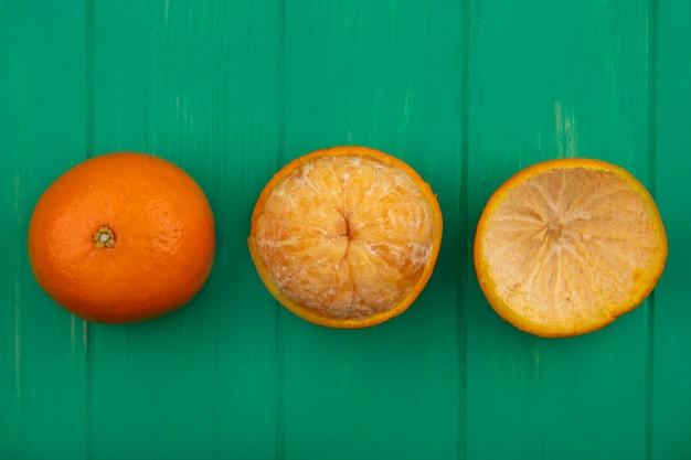 Вид сверху апельсин с очищенной кожурой на зеленом фоне