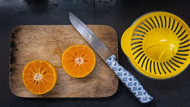 Вид сверху апельсинов и ножа для приготовления апельсинового сока на столе