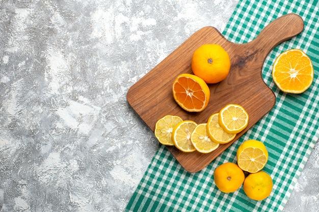 회색 테이블 여유 공간에 녹색 흰색 체크 무늬 식탁보에 레몬 커팅 보드에 상위 뷰 오렌지 레몬 조각