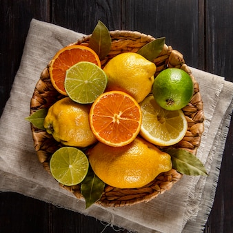 Top view of oranges and limes in basket