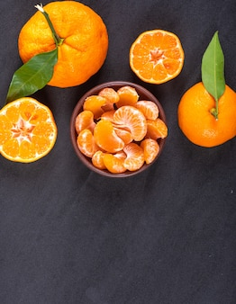 Top view oranges and mandarins on black stone surface