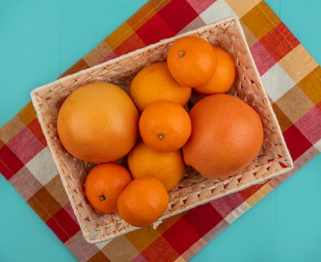 Vista dall'alto arance con pompelmo in un cesto su un asciugamano a scacchi su uno sfondo turchese