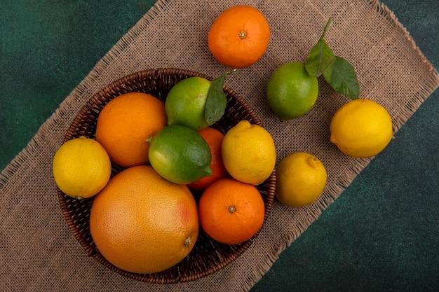Вид сверху апельсины с грейпфрутом, лимоном и лаймом в корзине на бежевой салфетке