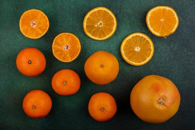 Vista dall'alto arance con pompelmo e mandarini su sfondo verde